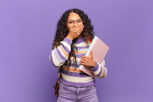 Jonge spaanse vrouw die mond bedekt met handen met een geschokte, verbaasde uitdrukking, een geheim houdt of oeps zegt. studentenconcept