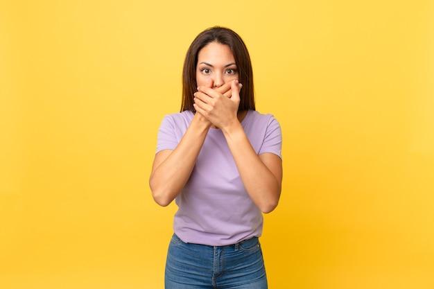 Jonge spaanse vrouw die mond bedekt met handen met een geschokte