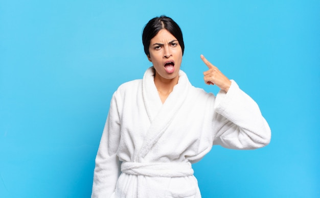 Jonge spaanse vrouw die naar de camera wijst met een boze agressieve uitdrukking die eruitziet als een woedende, gekke baas