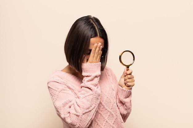 Jonge spaanse vrouw die ogen behandelt met handen met een droevige, gefrustreerde blik van wanhoop, huilend, zijaanzicht