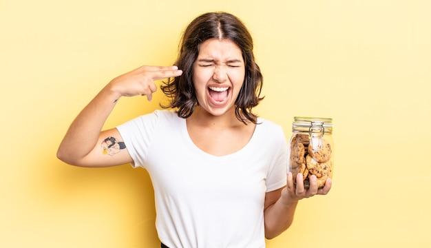 Jonge spaanse vrouw die ongelukkig en gestrest kijkt, zelfmoordgebaar dat pistoolteken maakt. koekjes fles concept