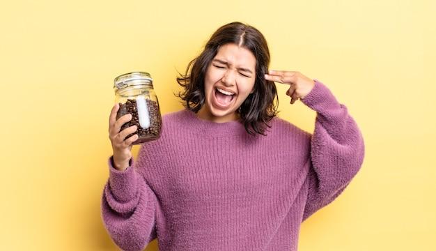 Jonge spaanse vrouw die ongelukkig en gestrest kijkt, zelfmoordgebaar dat pistoolteken maakt. koffiebonen concept