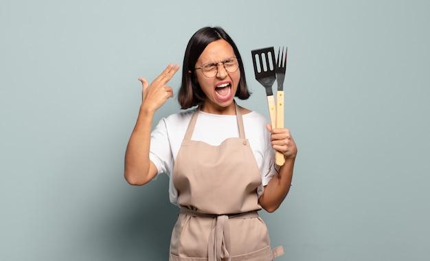 Jonge spaanse vrouw die ongelukkig en gestrest kijkt, zelfmoordgebaar die pistoolteken met hand maakt, naar hoofd wijst