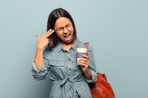 Jonge spaanse vrouw die ongelukkig en gestrest kijkt, zelfmoordgebaar die pistoolteken met hand maakt, wijst naar hoofd