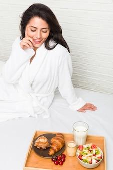 Jonge spaanse vrouw die ontbijt op het bed heeft