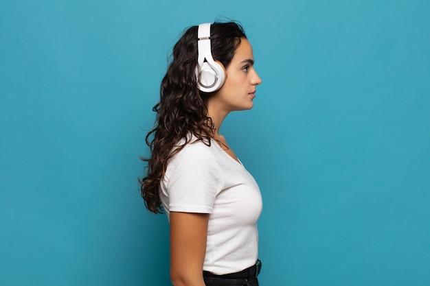 Jonge spaanse vrouw die op profielweergave ruimte vooruit wil kopiëren, denken, zich voorstellen of dagdromen