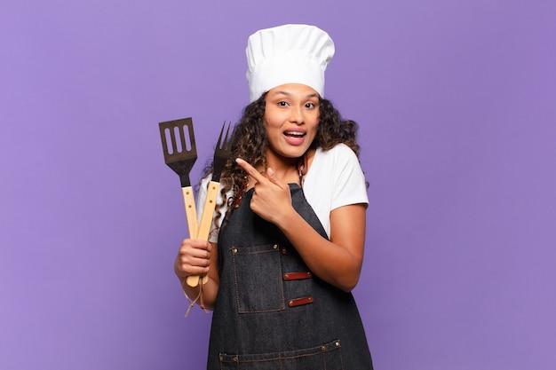 Jonge spaanse vrouw die opgewonden en verrast kijkt en naar de zijkant en naar boven wijst om ruimte te kopiëren. barbecue chef-kok concept