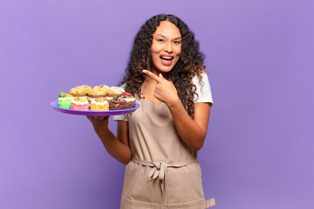 Jonge spaanse vrouw die opgewonden en verrast kijkt en naar de zijkant en naar boven wijst om ruimte te kopiëren. koken taarten concept