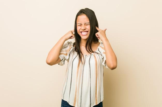 Jonge spaanse vrouw die oren behandelt met handen