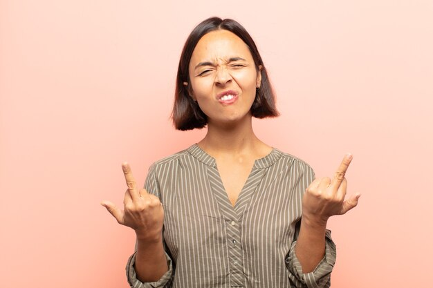 Jonge spaanse vrouw die provocerend, agressief en obsceen voelt, de middelvinger omdraait, met een rebelse houding