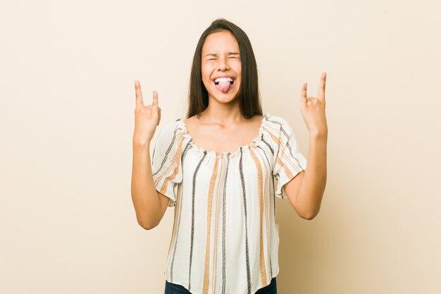 Jonge spaanse vrouw die rotsgebaar met vingers toont