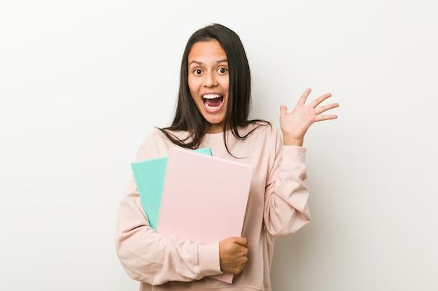 Jonge spaanse vrouw die sommige notitieboekjes houdt die een overwinning of een succes vieren