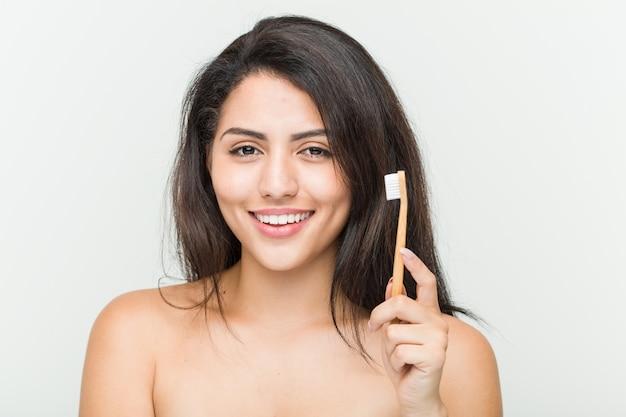 Jonge spaanse vrouw die tandenborstel glimlachen houden zeker met gekruiste wapens.