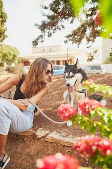 Jonge spaanse vrouw die tijd verdrijft met haar siberische husky in park