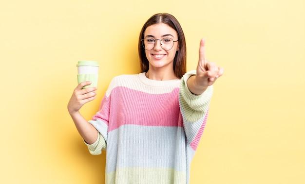 Jonge spaanse vrouw die trots en vol vertrouwen glimlacht en nummer één maakt. afhaal koffie concept