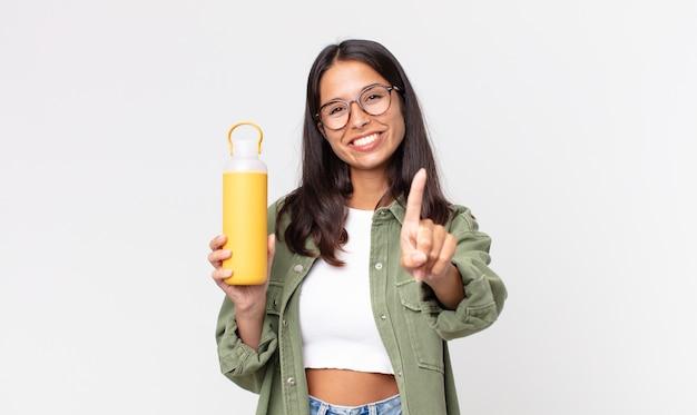 Jonge spaanse vrouw die trots en vol vertrouwen glimlacht en nummer één maakt en een koffiethermoskan vasthoudt