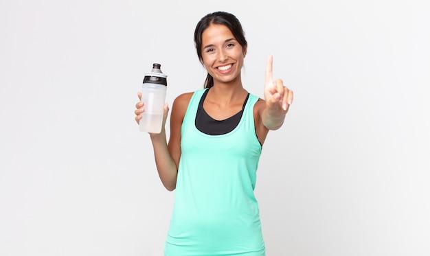 Jonge spaanse vrouw die trots en zelfverzekerd glimlacht en nummer één maakt en een waterfles vasthoudt. fitnessconcept