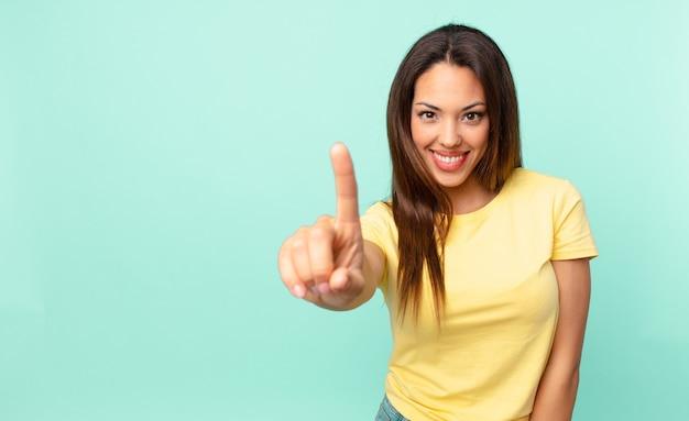 Jonge spaanse vrouw die trots en zelfverzekerd glimlacht en nummer één maakt