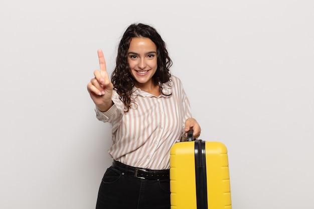 Jonge spaanse vrouw die trots en zelfverzekerd glimlacht en nummer één triomfantelijk laat poseren, zich een leider voelt