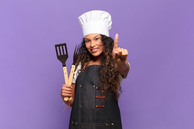 Jonge spaanse vrouw die trots en zelfverzekerd glimlacht en nummer één triomfantelijk poseert, voelt zich een leider. barbecue chef-kok concept