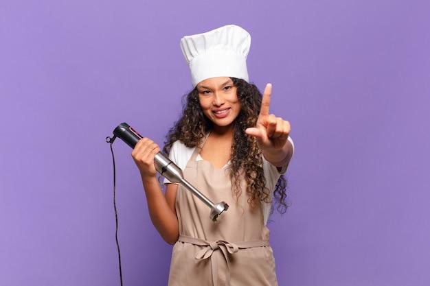 Jonge spaanse vrouw die trots en zelfverzekerd glimlacht en nummer één triomfantelijk poseert, voelt zich een leider. chef-kok concept