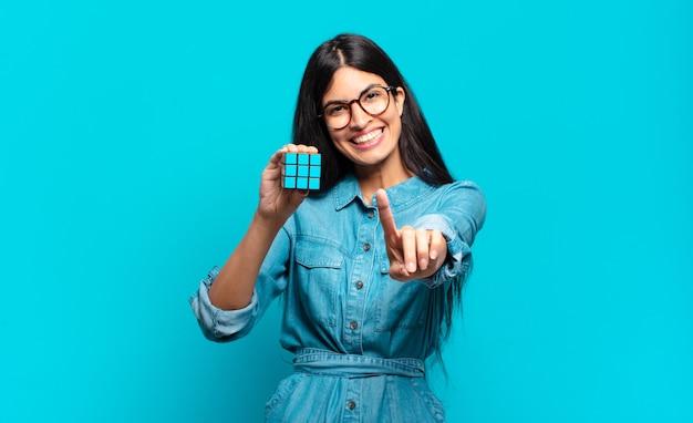 Jonge spaanse vrouw die trots en zelfverzekerd glimlacht en nummer één triomfantelijk poseert