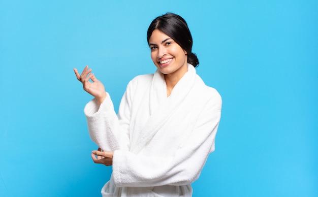 Jonge spaanse vrouw die trots en zelfverzekerd glimlacht, zich gelukkig en tevreden voelt en een concept op exemplaarruimte toont