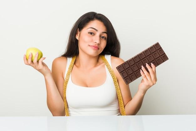 Jonge spaanse vrouw die tussen appel of chocoladetablet kiest