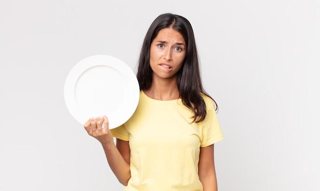 Jonge spaanse vrouw die verbaasd en verward kijkt en een leeg bord vasthoudt