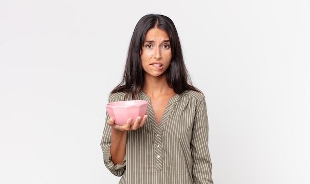 Jonge spaanse vrouw die verbaasd en verward kijkt en een lege kom of pot vasthoudt