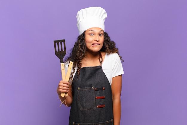 Jonge spaanse vrouw die verbaasd en verward kijkt, lip bijt met een nerveus gebaar, niet wetend het antwoord op het probleem. barbecue chef-kok concept