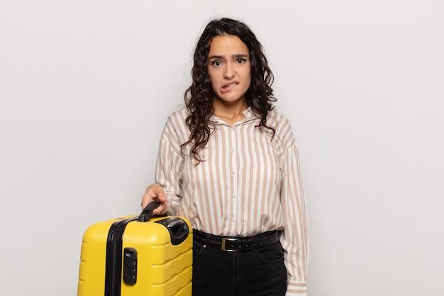 Jonge spaanse vrouw die verbaasd en verward kijkt, lip bijt met een nerveus gebaar, niet wetend het antwoord op het probleem