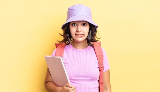 Jonge spaanse vrouw die verbaasd en verward kijkt. terug naar schoolconcept
