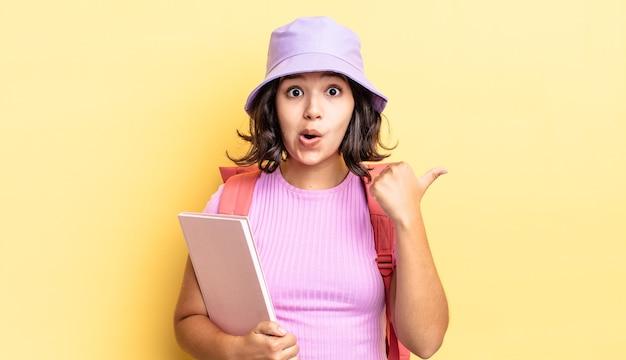 Jonge spaanse vrouw die verbaasd in ongeloof kijkt. terug naar schoolconcept