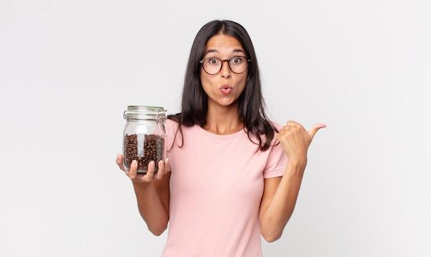 Jonge spaanse vrouw die verbaasd kijkt in ongeloof en een fles koffiebonen vasthoudt