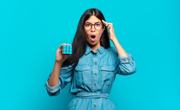 Jonge spaanse vrouw die verbaasd, met open mond, geschokt kijkt, een nieuwe gedachte, een nieuw idee of een concept realiseert. intelligentie probleem concept