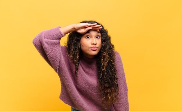 Jonge spaanse vrouw die verbijsterd en verbaasd kijkt, met hand over voorhoofd ver weg kijkend, kijkend of zoekend