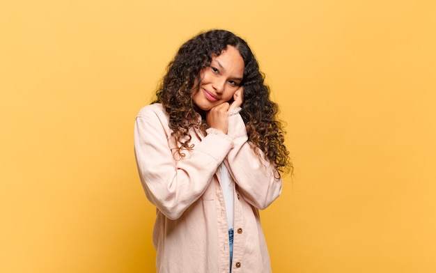 Jonge spaanse vrouw die verliefd is en er schattig, schattig en gelukkig uitziet, romantisch glimlachend met de handen naast het gezicht