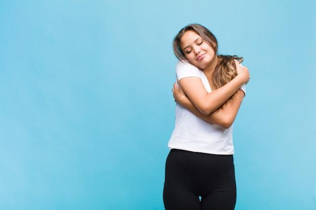 Jonge spaanse vrouw die verliefd is, lacht, knuffelt en zichzelf knuffelt, vrijgezel blijft, egoïstisch en egocentrisch is