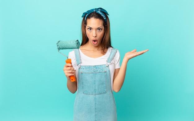 Jonge spaanse vrouw die verrast en geschokt kijkt, met open mond terwijl ze een object vasthoudt en een muur schildert