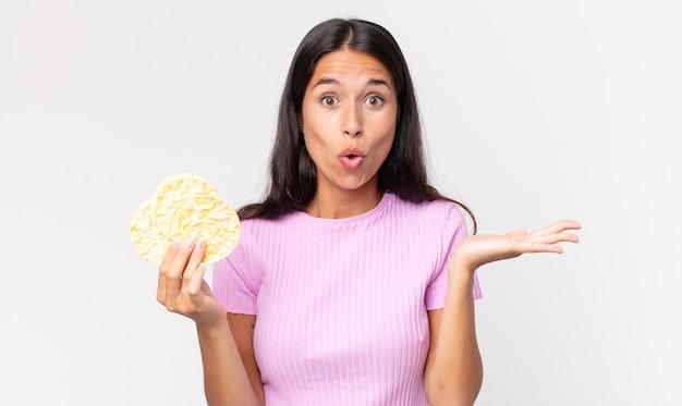Jonge spaanse vrouw die verrast en geschokt kijkt, met open mond terwijl ze een object vasthoudt en een rijstkoekje vasthoudt. dieet concept