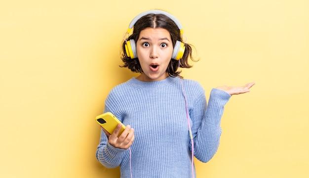 Jonge spaanse vrouw die verrast en geschokt kijkt, met open mond terwijl ze een object vasthoudt. koptelefoon en smartphone concept
