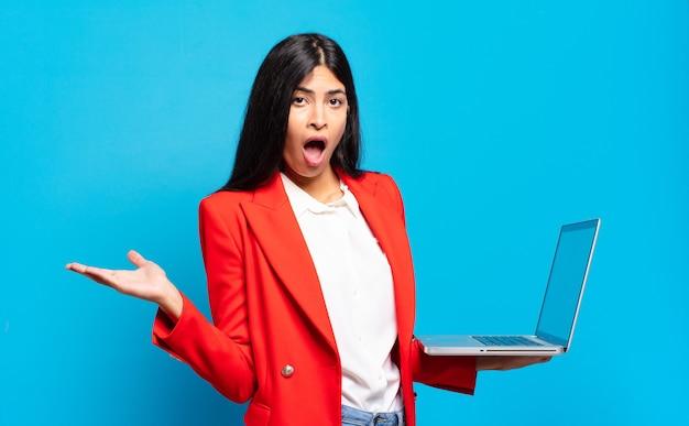 Jonge spaanse vrouw die verrast en geschokt kijkt, met open mond terwijl ze een object vasthoudt met een open hand aan de zijkant. laptopconcept