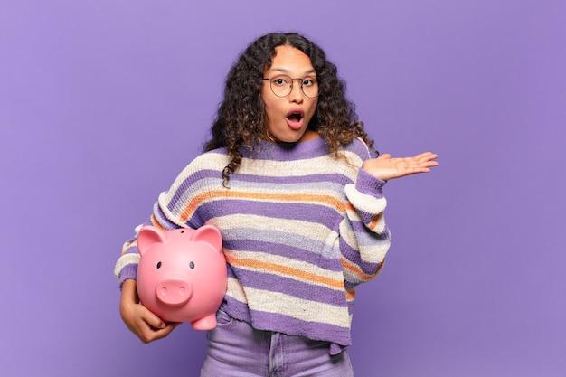 Jonge spaanse vrouw die verrast en geschokt kijkt, met open mond terwijl ze een object vasthoudt met een open hand aan de zijkant