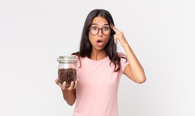 Jonge spaanse vrouw die verrast kijkt, een nieuwe gedachte, idee of concept realiseert en een fles koffiebonen vasthoudt