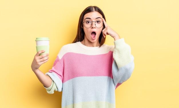 Jonge spaanse vrouw die verrast kijkt en een nieuwe gedachte, idee of concept realiseert. afhaal koffie concept