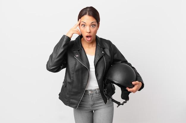 Jonge spaanse vrouw die verrast kijkt en een nieuwe gedachte, idee of concept realiseert. motorrijder concept