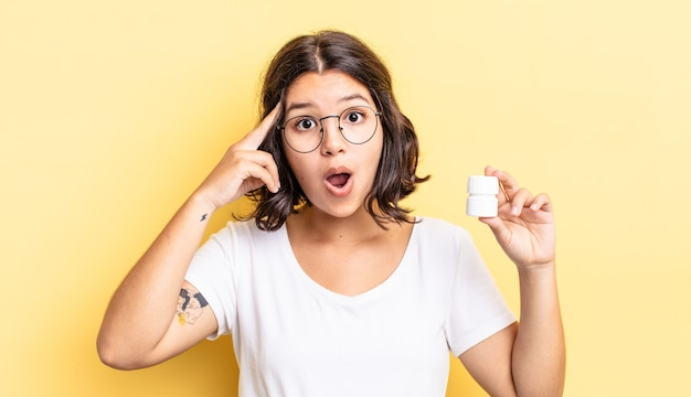 Jonge spaanse vrouw die verrast kijkt en een nieuwe gedachte, idee of concept realiseert. ziekte pillen concept