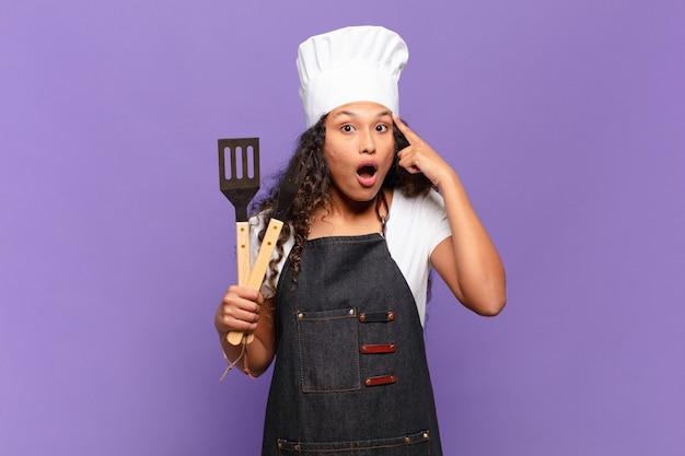 Jonge spaanse vrouw die verrast, met open mond, geschokt kijkt en een nieuwe gedachte, idee of concept realiseert. barbecue chef-kok concept