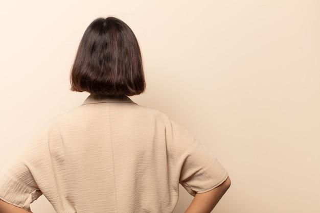 Jonge spaanse vrouw die verward of vol of twijfels en vragen voelt, zich afvraagt, met de handen op de heupen, zicht naar achteren